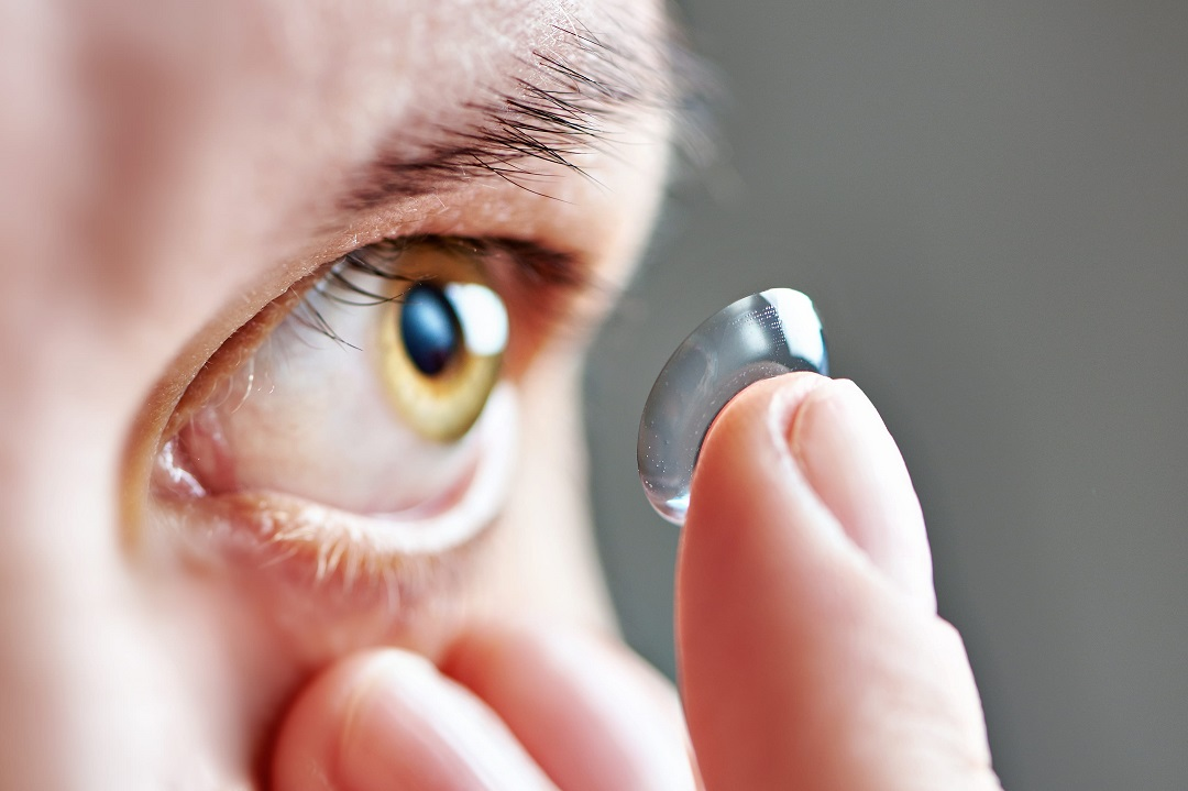 A person putting on a contact lens.